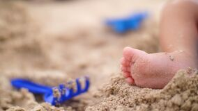 Zachte nadruk, a-close-up van uiterst klein, weinig babyvoet op een zandachtergrond, is er dichtbij speelgoed stock videobeelden