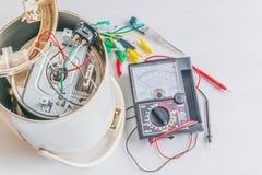 Zachte nadruk de schade van de elektrische ketel met vaag van de multimeter, schroevedraaier, mechanisch hulpmiddel, op de witte  royalty-vrije stock fotografie