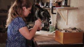 Zachte nadruk Het meisje schildert een houten punt met een borstel stock video