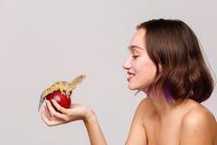 Zachte nadruk isolatie binnen De jonge en donkerbruine appel van de meisjesholding waarop een gekko zit stock afbeelding