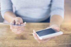 Zachte nadruk van hand van vrouwelijke holdings mobiele telefoon en kredietauto Stock Foto