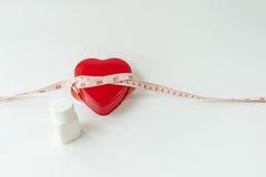 Zachte nadruk van maatregelenband rond rood die hart met pil op wit wordt geïsoleerd Stock Foto