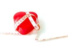 Zachte nadruk van maatregelenband rond rood die hart met pil op wit wordt geïsoleerd Stock Afbeelding