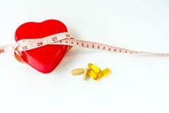 Zachte nadruk van maatregelenband rond rood die hart met pil op wit wordt geïsoleerd Stock Fotografie