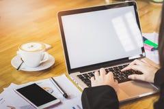 Zachte nadruk van vrouwenhand die met telefoon en laptop aan houten bureau in bureau in ochtendlicht werken Royalty-vrije Stock Foto