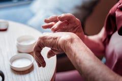 Zachte oude vrouw die roze blouse dragen en haar handen behandelen royalty-vrije stock afbeeldingen
