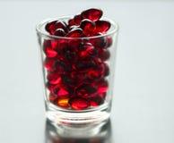 Zachte rode pillen op a in een glas stock afbeeldingen