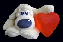 Zachte stuk speelgoed hond hebben zij een hart Isoleer op zwarte achtergrond stock foto