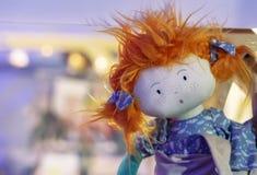 Zachte stuk speelgoed pop met rood haar en purpere kleding stock foto's