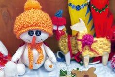 Zachte stuk speelgoed sneeuwman in een oranje hoed en een sjaal stock foto's