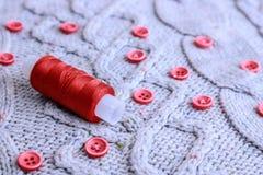 Zachte warme natuurlijke sweater, stoffen met een gebreid patroon van garen en rode kleine ronde knopen voor het naaien en een st royalty-vrije stock foto