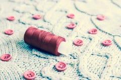 Zachte warme natuurlijke sweater, stoffen met een gebreid patroon van garen en rode kleine ronde knopen voor het naaien en een st royalty-vrije stock foto's