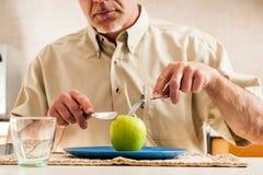 Zaciemniający mężczyzna przecinania jabłko nad błękita talerzem obrazy royalty free