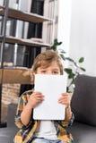zaciemniający widok chłopiec mienia patrzeć kamerę i pastylka obraz stock