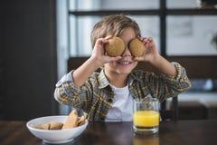 zaciemniający widok chłopiec nakrycie ono przygląda się z ciastkami w rękach podczas gdy mieć śniadanie obrazy stock