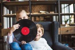 zaciemniający widok dzieciaki patrzeje kamerę z winylowym rejestrem obraz royalty free