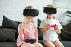 zaciemniający widok dzieciaki w rzeczywistość wirtualna słuchawkach bawić się gra wideo na kanapie fotografia royalty free