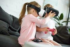 zaciemniający widok dzieciaki w rzeczywistość wirtualna słuchawkach bawić się gra wideo na kanapie obraz stock