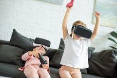 zaciemniający widok dzieciaki w rzeczywistość wirtualna słuchawkach bawić się gra wideo na kanapie obrazy stock