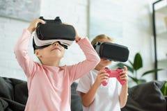 zaciemniający widok dzieciaki w rzeczywistość wirtualna słuchawkach bawić się gra wideo na kanapie zdjęcie royalty free