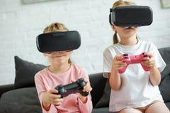 zaciemniający widok dzieciaki w rzeczywistość wirtualna słuchawkach bawić się gra wideo na kanapie zdjęcia royalty free