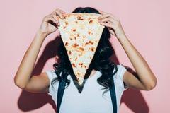 zaciemniający widok kobiety nakrycia twarz z kawałkiem pizza obraz stock