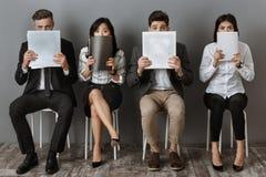zaciemniający widok wielokulturowi ludzie biznesu czeka akcydensowego wywiad z falcówkami i notatniki zdjęcie stock
