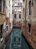Zaciszność wąski kanał w Venice otaczał malowniczymi antycznymi budynkami odbijającymi w wodzie zdjęcie stock
