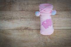 Zacken Sie gestrickte Socken für Baby auf dem Bretterboden aus Retro- vinta Stockbilder