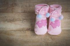 Zacken Sie gestrickte Socken für Baby auf dem Bretterboden aus Retro- vinta Stockfoto