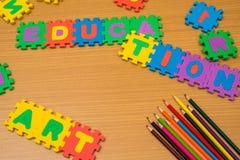 Zackiger Bildungshintergrund und multi farbige Bleistifte Stockfotos
