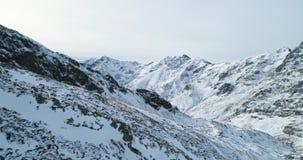 Zacofana antena nad zima śnieżnym przełęczem z mountaineering narciarki ludźmi chodzi w górę pięcia Śnieg zakrywający zbiory