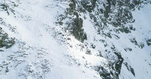 Zacofany odkrywa antenę nad zimy śnieżną górą z mountaineering narciarki ludźmi chodzi w górę pięcia Śnieg zakrywający zbiory