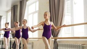 Zaczynać tancerze robią ćwiczeniom przy baletniczym barre w przestronnej sala balowej, ich nauczyciel w leotard pomagają zbiory