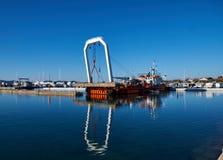 Zadar, Хорватия, 29-ое ноября 2018 Кран системы рычагов на замененной части баржи поднимаясь конкретной пристани будучи сокрушанн стоковые фото