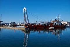Zadar, Хорватия, 29-ое ноября 2018 Кран системы рычагов на замененной части баржи поднимаясь конкретной пристани будучи сокрушанн стоковое изображение rf