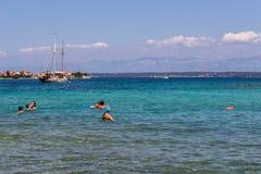 Croatian best beach Dalmatia transparent waters. Zadar, Croatia - July 24, 2018: People swimming in the transparent waters of Ugljan island stock images