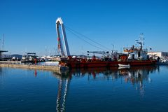 Zadar, Croatia, November 29, 2018. Leverage crane on barge lifting part of concrete pier being demolished and replaced. Crane removing large piece of concrete royalty free stock image