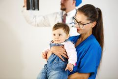 Zadawalający dziecko w rękach lekarka w tle lekarka patrzeje promieniowanie rentgenowskie Biały tło obraz stock