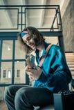 Zadawalający ciemnowłosy inspirowany mężczyzna w błękitnej bluzy sportowej przewożenia gitarze zdjęcie royalty free