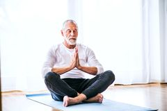 Zadawalający starszy mężczyzna medytuje w domu zdjęcia stock