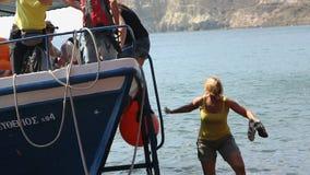 Zadawalający z dennymi wycieczkowymi turystami iść w dół od łodzi brzeg czerwieni plaża zbiory
