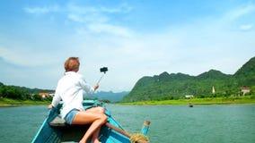 Zadek dziewczyna robi selfie obsiadaniu na łódkowatym łęku przeciw rzece zbiory