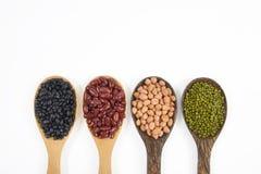 Zaden beansBlack Boon, Rode Boon, Pinda en Mung Boon nuttig voor gezondheid in houten lepels op witte achtergrond royalty-vrije stock afbeeldingen