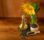 Zaden, olie en zonnebloembloem op een houten achtergrond stock afbeelding