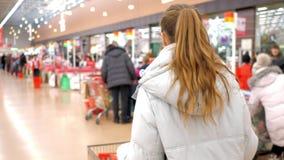 Zadka widoku kobieta z produktami chodzi kasjera biurko zdjęcie wideo