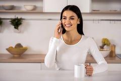 Zadowolona ładna kobieta opowiada na telefonie obraz royalty free