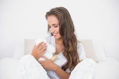 Zadowolona atrakcyjna brunetka trzyma miękką zabawkę Fotografia Stock