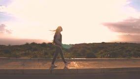 Zadowolona blondynki dziewczyna chodzi pewnie wzdłuż drogi, utrzymuje jej ręki w kieszeni, moda model z długim złotym włosy zbiory
