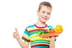 zadowolona ch?opiec z talerzem zdrowi warzywa odizolowywaj?cy na bia?ym tle zdjęcia royalty free